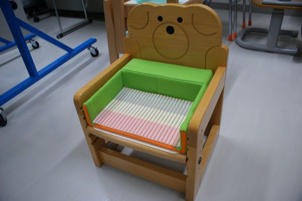作業療法士の先生にアドバイスをいただきながら、おひさまの先生が作ったオリジナルの椅子です。姿勢保持が難しい子でも座りやすいように工夫されています。高価なものでなくても、牛乳パックなど身近にあるもので作ることができます。